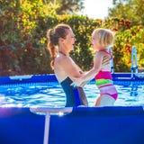 Glückliche gesunde Mutter und Kind beim Swimmingpoolspielen Stockbilder