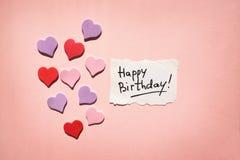 Glückliche Glückwunschkarte mit Text und Herzen auf schönem rosa Hintergrund stockfoto