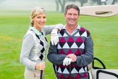 Glückliche Golf spielende Paare mit Golfbuggy hinten stockfotografie