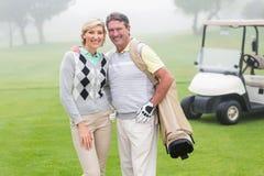 Glückliche Golf spielende Paare mit Golfbuggy hinten lizenzfreies stockbild