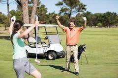 Glückliche Golfspielerpaare mit den Armen angehoben Lizenzfreie Stockfotografie