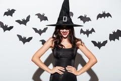 Glückliche gotische Frau in der Hexenhalloween-Kostümstellung und -c$lächeln stockbilder