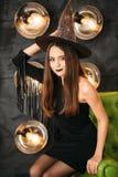 Glückliche gotische junge Frau in Hexenhalloween-Kostüm mit dem Hut, der am Stuhl sitzt stockbilder