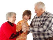 Glückliche Großeltern und Enkelin spielen den Dummkopf Stockfotos