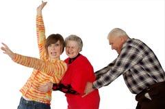 Glückliche Großeltern und Enkelinspieldummkopf Lizenzfreie Stockfotografie