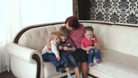 Glückliche Großmutter, die mit ihren Enkelkindern umarmt stock video footage