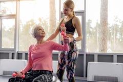 Glückliche Großmutter, die mit Trainer in der Turnhalle sagt lizenzfreie stockbilder