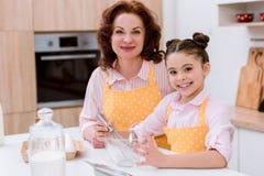 glückliche Großmutter mit der kleinen zusammen kochenden und schauenden Enkelin lizenzfreie stockfotos