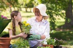 Glückliche Großmutter mit ihrer Enkelingartenarbeit Lizenzfreies Stockfoto