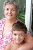 Glückliche Großmutter und Enkel, die zusammen Kamera betrachtet Lizenzfreie Stockbilder