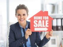 Glückliche Grundstücksmaklerfrau, die nach Hause für Verkaufszeichen darstellt Stockbild