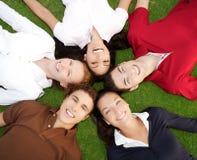 Glückliche Gruppe der Freunde im Kreis zusammen auf Gras Lizenzfreies Stockfoto