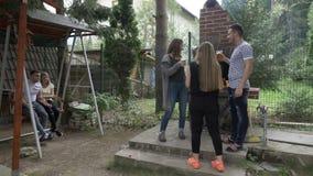Glückliche Gruppe Freunde, die röstendes und trinkendes Bier des Grillgrills Partei des Sommers an der im Freien zubereiten stock footage