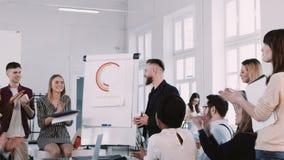 Glückliche Gruppe Geschäftsleute klatschen zum mittleren gealterten Trainermann bei der modernen hellen Bürositzung Zeitlupe ROTE stock video