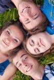 Glückliche Gruppe junge Leute u. grünes Gras Stockfotografie