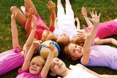 Glückliche Gruppe Kinder, die auf dem Boden in einem Kreis liegen Lizenzfreies Stockbild