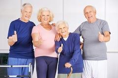 Glückliche Gruppe Senioren, die Daumen hochhalten Stockbilder