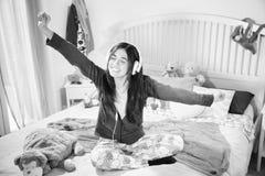 Glückliche hörende Musik der jungen Frau mit Kopfhörer im Schlafzimmer stockbild