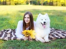 Glückliche hübsche Frau des Porträts und weißer Samoyedhund Stockbilder
