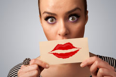 Glückliche hübsche Frau, die Karte mit Kusslippenstiftkennzeichen hält Lizenzfreie Stockbilder