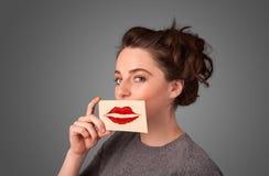 Glückliche hübsche Frau, die Karte mit Kusslippenstiftkennzeichen hält Lizenzfreie Stockfotos