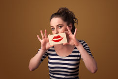 Glückliche hübsche Frau, die Karte mit Kusslippenstiftkennzeichen hält Stockbild