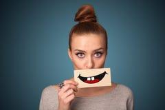 Glückliche hübsche Frau, die Karte mit lustigem smiley hält lizenzfreie stockfotos