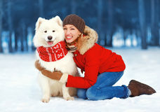 Glückliche hübsche Frau, die Spaß mit weißem Samoyedhund draußen im Park an einem Wintertag hat Lizenzfreies Stockbild