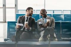 glückliche hübsche Geschäftskollegen, die auf Flug im Flughafen warten Lizenzfreie Stockfotos
