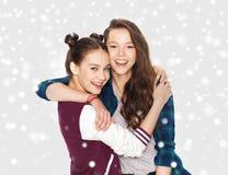 Glückliche hübsche Jugendlichen, die über Schnee umarmen Lizenzfreie Stockfotos