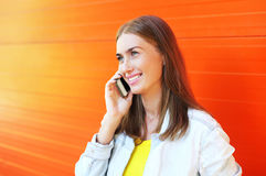 Glückliche hübsche lächelnde Frau des Porträts, die auf Smartphone spricht stockbild