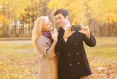 Glückliche hübsche lächelnde junge Paare, die draußen Bildselbstporträt auf smarphone im sonnigen Herbst nehmen stockbild