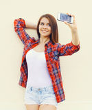Glückliche hübsche Mädchenabnutzung ein kariertes rotes Hemd und kurze Hosen macht Selbstporträt auf dem Smartphone Lizenzfreies Stockbild