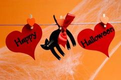 Glückliche Halloween-Mitteilung geschrieben über rote Herzen und schwarze Katze mit den Klammern, die von einer Linie hängen Lizenzfreies Stockbild