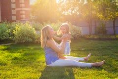 Glückliche harmonische Familie draußen bemuttern Sie das Lachen und das Spielen mit Babytochtermädchen im Sommer auf der Natur Stockbilder