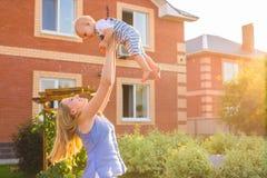 Glückliche harmonische Familie draußen bemuttern Sie Wurfsbaby oben und im Sommer auf der Natur lachen und spielen Stockfoto
