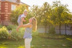 Glückliche harmonische Familie draußen bemuttern Sie Wurfsbaby oben und im Sommer auf der Natur lachen und spielen Stockbild