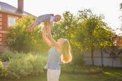 Glückliche harmonische Familie draußen bemuttern Sie Wurfsbaby oben und im Sommer auf der Natur lachen und spielen Lizenzfreies Stockbild