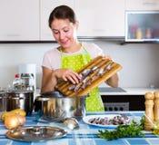 Glückliche Hausfrau, die neues Rezept versucht Stockfoto