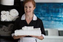 Glückliche Hausgehilfin mit weißen Tüchern lizenzfreie stockbilder