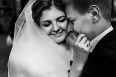 Glückliche herrliche blonde Braut und stilvoller hübscher Bräutigam, die w umarmt Stockfotografie