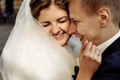 Glückliche herrliche blonde Braut und stilvoller hübscher Bräutigam, die w umarmt Stockfotos