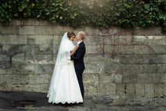 Glückliche herrliche blonde Braut und stilvoller hübscher Bräutigam mit wahrem Stockfoto