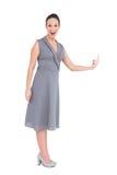 Glückliche herrliche Frau im noblen Kleid ihren Finger oben zeigend Stockfoto