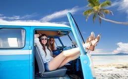 Glückliche Hippiefrauen im Mehrzweckfahrzeugauto auf Sommer setzen auf den Strand Stockbild