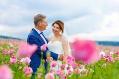 Glückliche Hochzeitspaare auf dem rosa Mohnblumengebiet stockbild