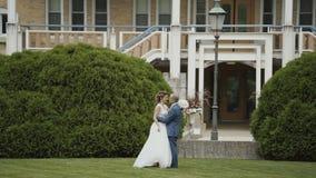 Glückliche Hochzeitspaare gehen in Richtung zu einander und küssend auf dem Hintergrund des luxuriösen mansoin stock video