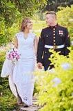 Glückliche Hochzeitspaare im Garten lizenzfreies stockfoto