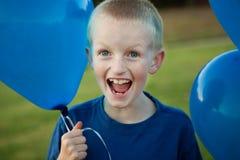 Glückliche Holdingballone des kleinen Jungen Stockbilder