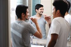 Glückliche homosexuelle Paar-bürstende Zähne im Badezimmer stockfoto
